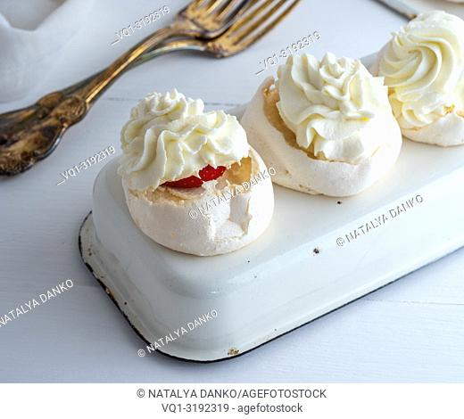 baked meringue with cream and fresh strawberries on an iron tray, close up
