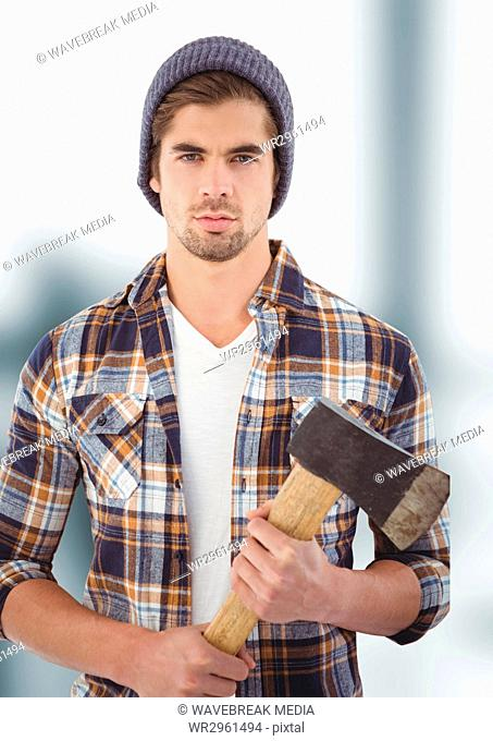 Confident hipster holding ax over blurred background