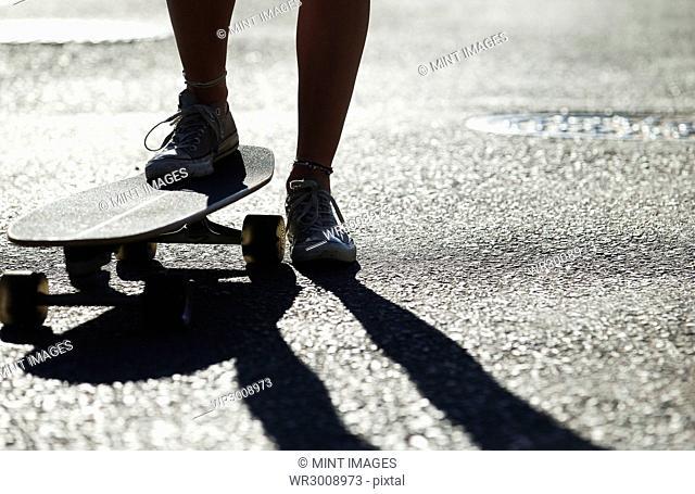 Feet of a person riding a skateboard on an asphalt road surface