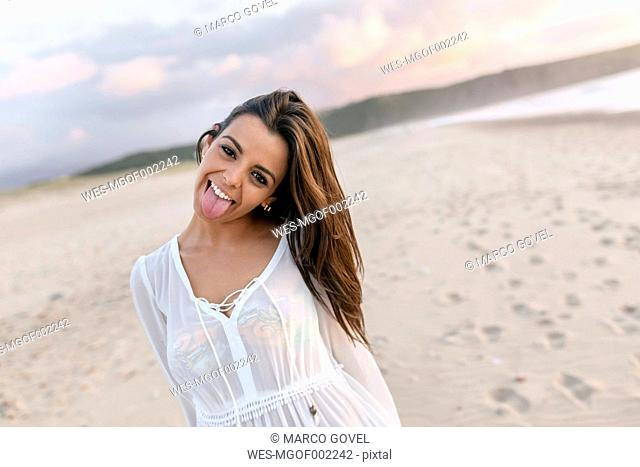 Portrait of young woman at beach, sticking out tongue