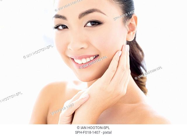 MODEL RELEASED. Young Asian woman with hands touching face, portrait