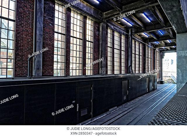 New York City, Manhattan, High Line Park. Looking North in the Chelsea Marketplace Passage at Original Railroad Tracks and Old Windows