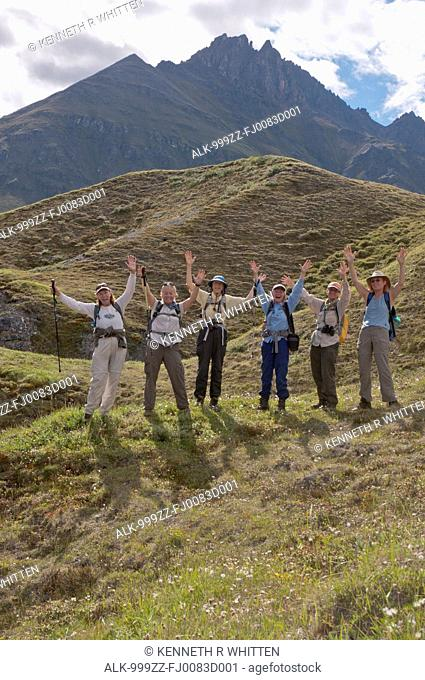 Mature female hikers with arms raised and having fun on ridge above the Marsh Fork of the Canning River in the Brooks Range, Arctic National Wildlife Refuge