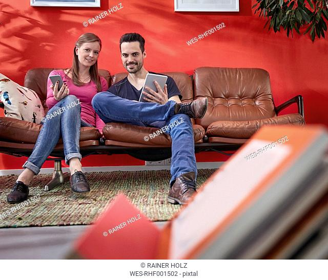 Young businessman and woman sitting on vintage couch using digital gadgets