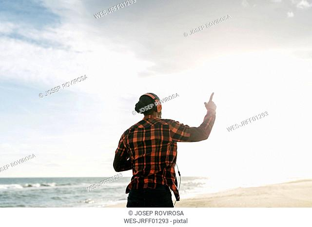 Back view of man walking on the beach listening music with headphones