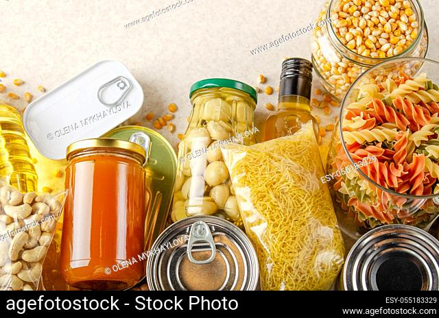 Flat lay view at kitchen table full with non-perishable foods. Spase for text