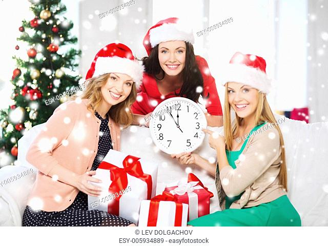 christmas, x-mas, winter, happiness concept - three smiling women in santa helper hats with clock showing 12 and gift boxes