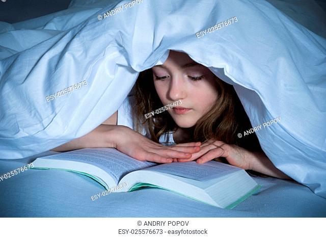 Cute Girl Reading Book Under The Blanket In Bedroom