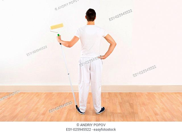 Rear view of young man holding paint roller while standing against white wall at home