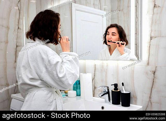 beautiful happy woman in white bathrobes brushing teeth in front of mirror in bathroom