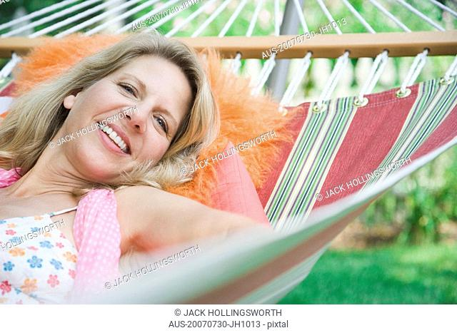 Portrait of a mature woman lying in a hammock and smiling