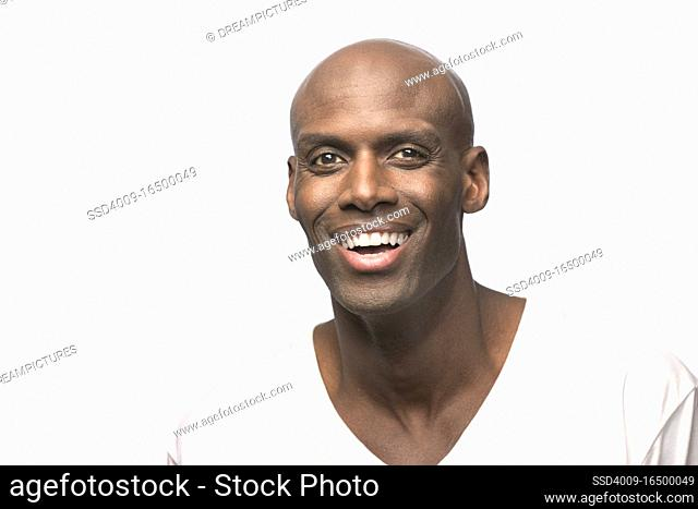 Portrait of young bald African American man looking at camera smiling