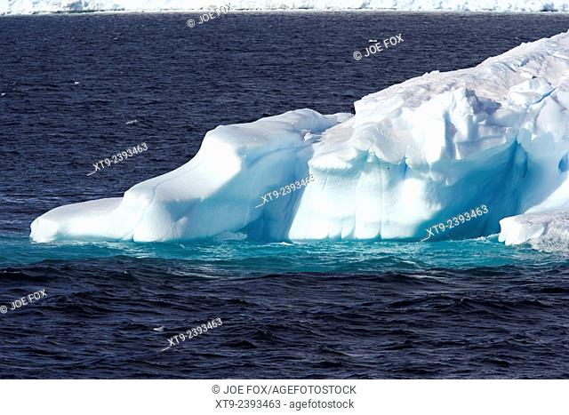 blue iceberg sculpted by wind and tide arctowski peninsula Antarctica