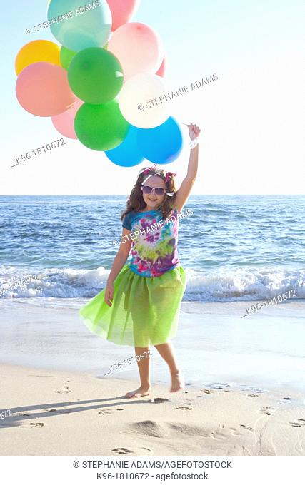 young girl walking towards camera on the beach holding balloons