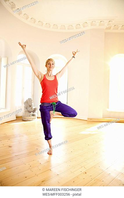 Happy woman in sunny yoga studio holding tree pose