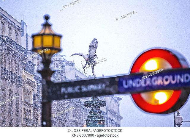 Snowing, Underground sign, Subway, on background The Angel of Christian Charity, Anteros, on Shaftesbury Memorial Fountain, by Alfred Gilbert, Piccadilly Circus