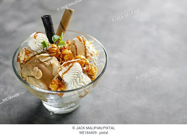 caramel and almond ice cream with caramelized popcorn sundae dessert in glass bowl