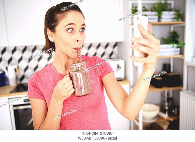 Portrait of young woman taking selfie with smartphone in the kitchen while drinking smoothie