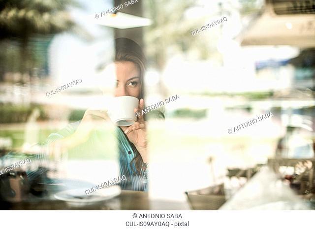 Woman drinking coffee at reflective cafe window, Dubai, United Arab Emirates