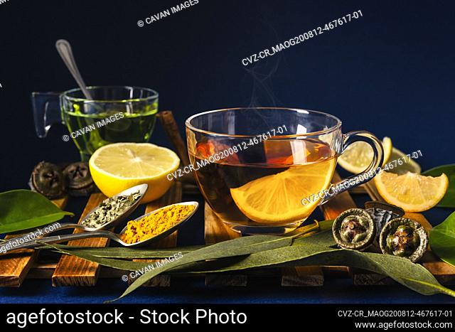Cup of tea with a slice of lemon with eucalyptus, lemons and spices