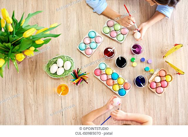 Overhead view of woman and daughter's hands painting easter eggs at table