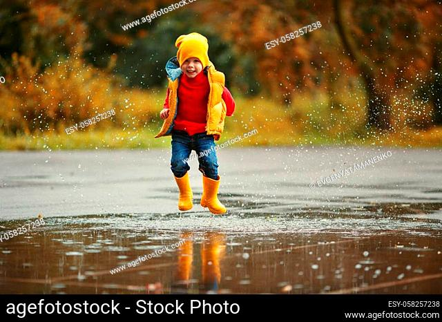 happy child baby boy with rubber boots jump in puddle on an autumn walk