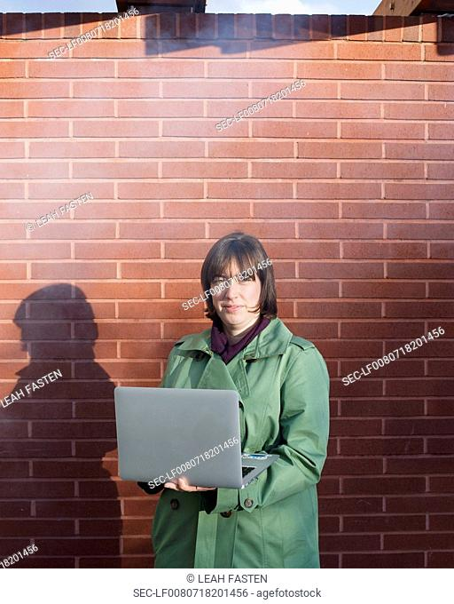 Woman with laptop standing by brick wall