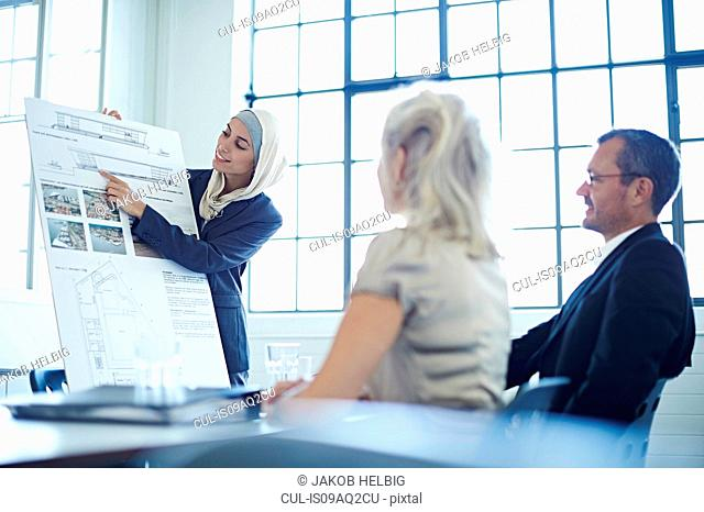 Young businesswoman presenting ideas to business team in office