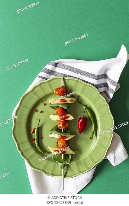 Macaroni with tomato sauce on green background