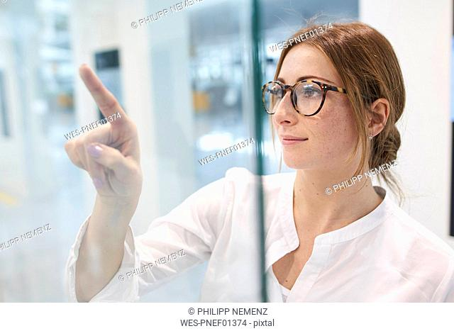 Young businesswoman touching virtual touchscreen