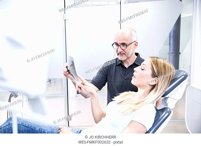 Dentist showing x-ray image to patient, sitting in dentist's chair