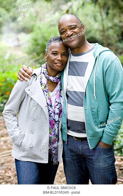 Smiling African American couple hugging in park