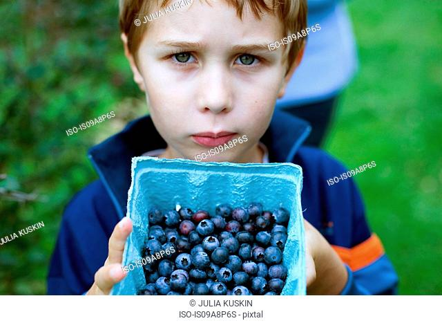 Boy with box of blueberries