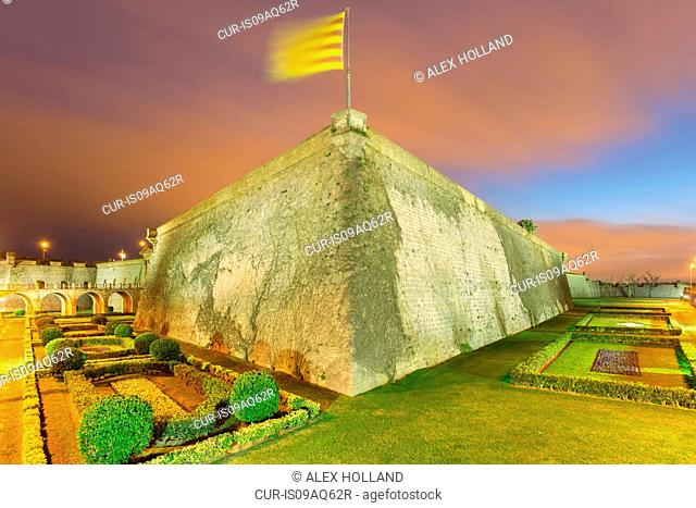 Catalan flag on wall of Montjuic Castle at night, Barcelona, Catalonia, Spain