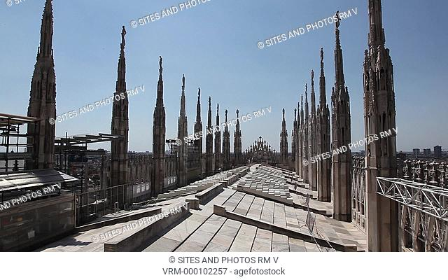 Exterior, Locked Down Shot, daylight, view of the cathedral's roof west section. Seen are the spires and the city of Milan