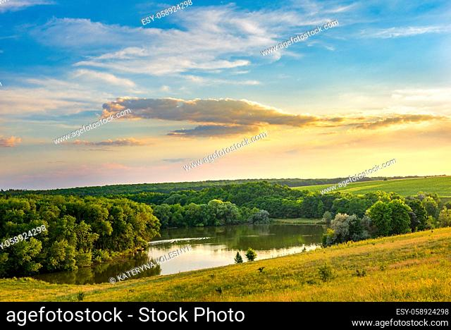 Calm lake in forest among hills at sunset