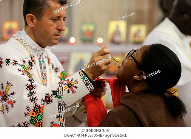 Melkite (Greek-catholic) priest giving holy communion in Sainte Foy church