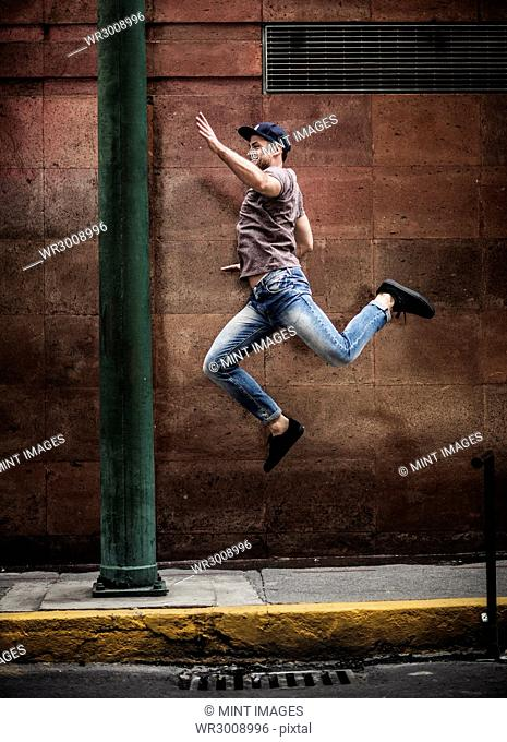 A man dancing on a sidewalk in front of a wall