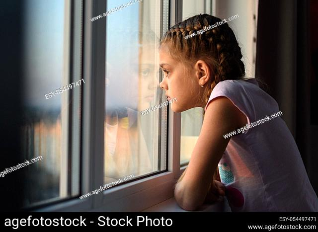 Eleven-year-old girl in isolation from boredom looks out the window