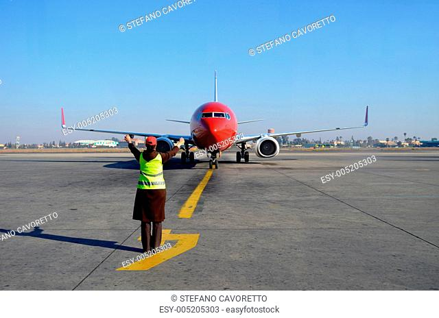 Woman signaling plane at airport