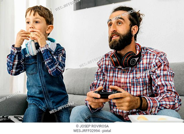 Portrait of father and son on the couch playing computer game
