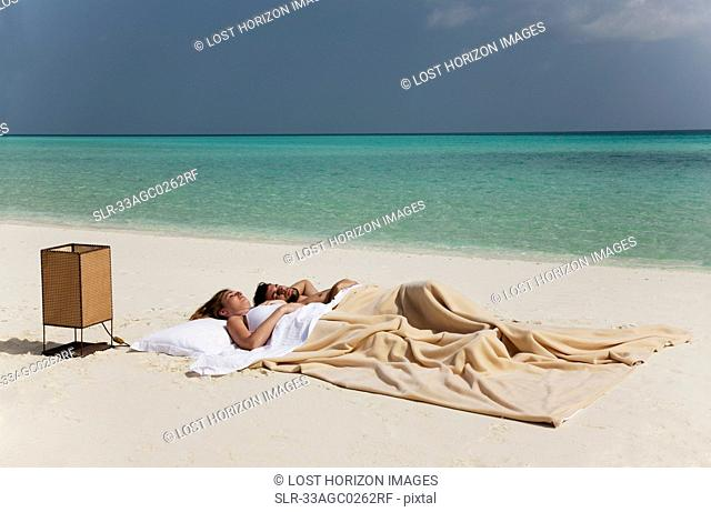 Couple sleeping in bed on beach