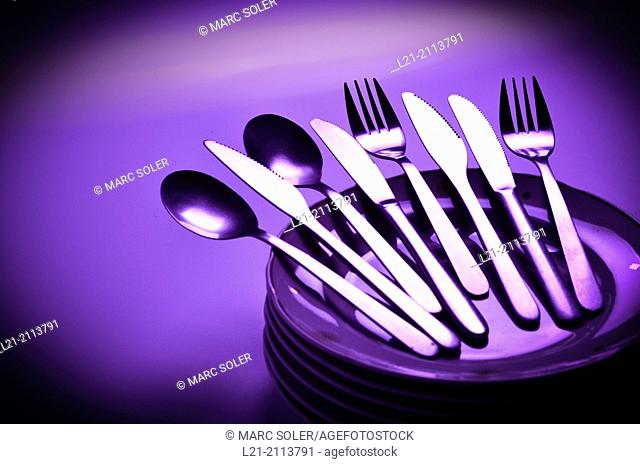 Cutlery on a stack of dishes