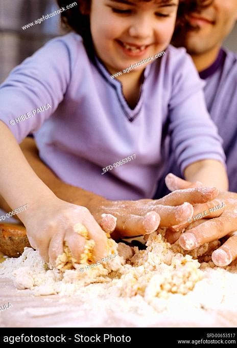 Girl kneading dough with her father