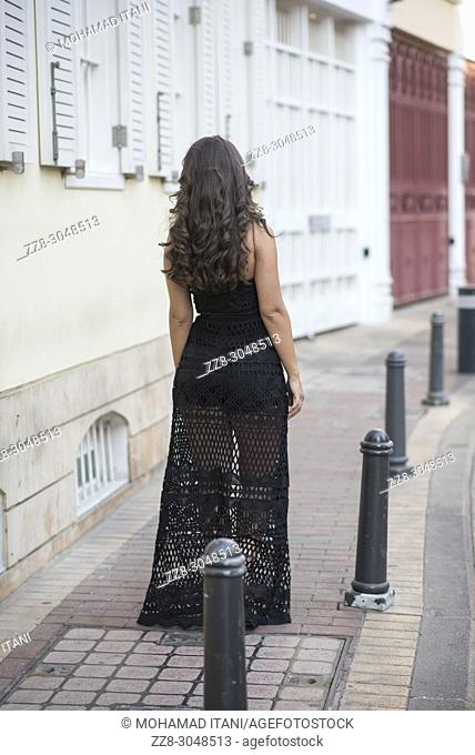 Beautiful young woman wearing a sexy dress standing on the street