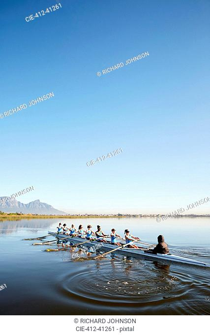 Female rowers rowing scull on tranquil lake under blue sky