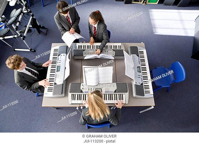 High school students playing piano in music class