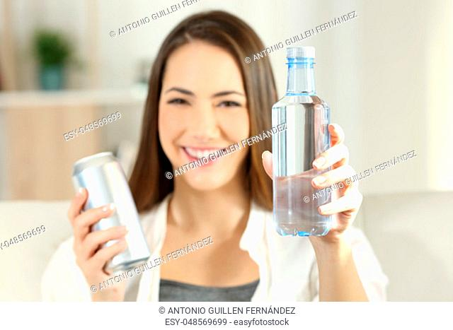 Front view portrait of a happy woman showing a bottle of water and a soda can sitting on a couch in the living room at home