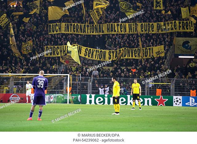 Dortmund fans hold up a banner that reads 'Auch international halten wir Eure Plätze frei!' (lit. 'Even internationally we hold your seats! Persevere - section...