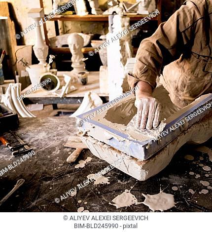 Caucasian artist scraping plaster in mold